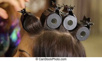 time in a beauty salon. Young woman in a beauty salon, hairdresser doing hairstyle to beautiful model