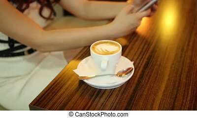 Female hands closeup with phone and cup of coffee. Young...