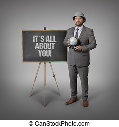 Its all about you text on blackboard with businessman...