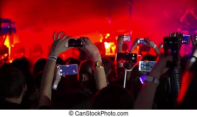 Crowd entertained and making party at concert and held over his head phones and tablets with digital displays
