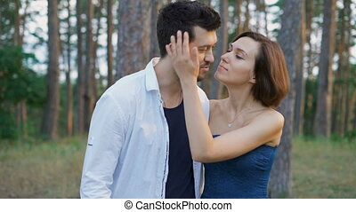 Start a romantic relationship. Attractive man and woman strolling together in the woods.
