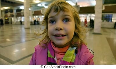 portrait of little cute caucasian girl standing in ticket office
