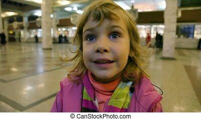portrait of little cute caucasian girl standing in ticket office