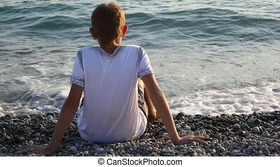 young boy sits on pebble beach and looks at sea, back view