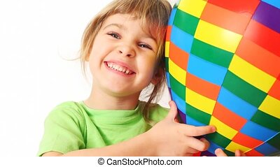 girl embraces toy varicoloured air ball and smile on white...