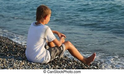 young boy sits on pebble beach and looks at sea, back-side...