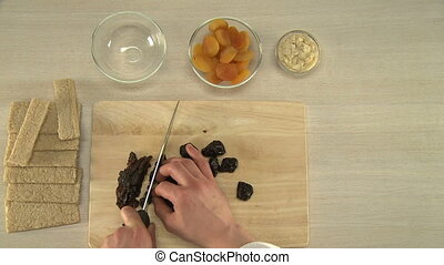 Prunes cutting for a cake. - Cook cutting prunes for a...