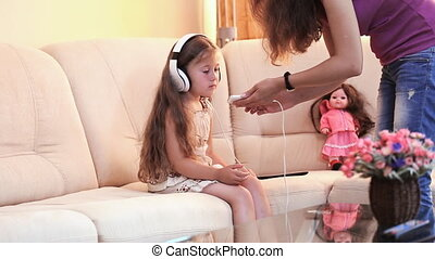 baby with headphones - little girl listens to music through...