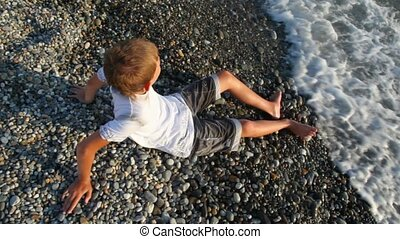 young boy sits on pebble beach and looks at sea, top view