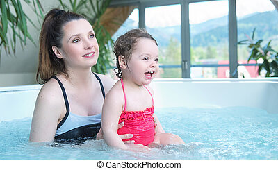 Mother and baby relaxing in a small swimming pool