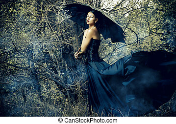 windy day - Magnificent brunette woman wearing long black...