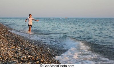 young boy running on pebble beach to camera, sea surf in background