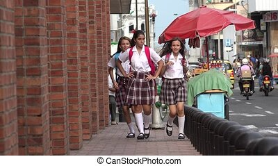 Female Teen Students Running On Sidewalk
