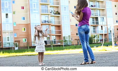Mother photographing her daughter telephone