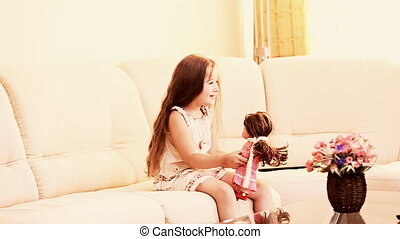 little girl plays with a doll sitting on the couch