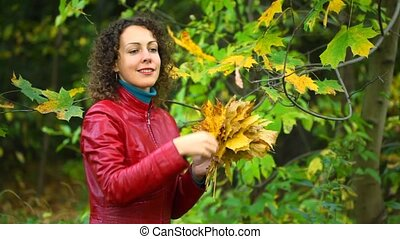 young woman gathering maple leaves from tree in autumn park
