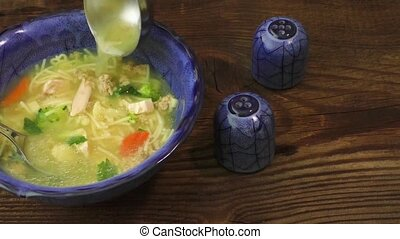 Chicken soup with vegetables in a blue bowl