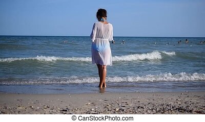 Girl or woman in white dress standing on beach