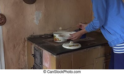 wench woman take cooked dumplings from boiling pot on furnace stove. 4K