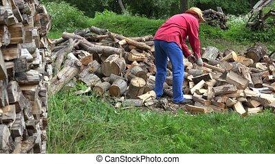 worker man split log near wood pile in garden at summertime....