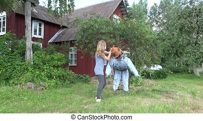 woman stand scarecrow on cherry tree to protect berries from...