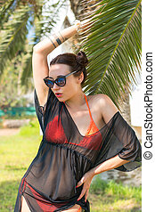 Beautiful woman in an orange swimsuit, sunglasses, and a...
