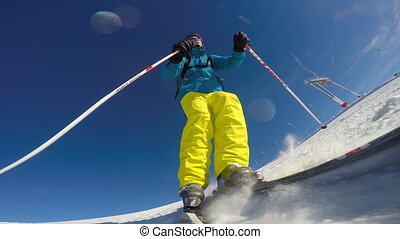 Alpine skier skiing slalom, camera on ski, blue sky on...