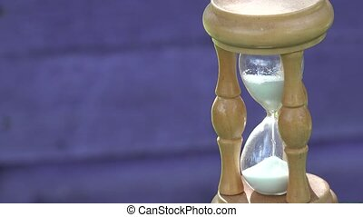 wooden sand glass with white sand on blurred purple wood background. 4K