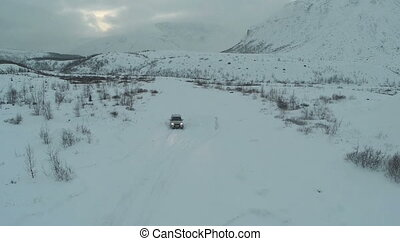 Car Driving through the Field in Winter