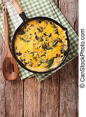 Italian omelette with spinach, cheese and mushrooms in a pan...