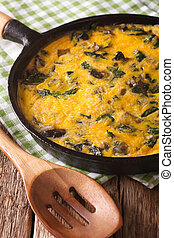 fritatta with spinach, cheddar cheese and mushrooms in a...
