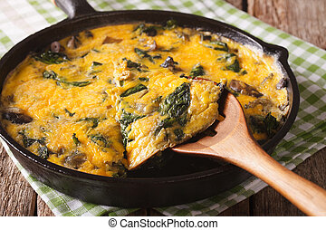 Delicious omelette with spinach, cheddar and mushrooms in a...