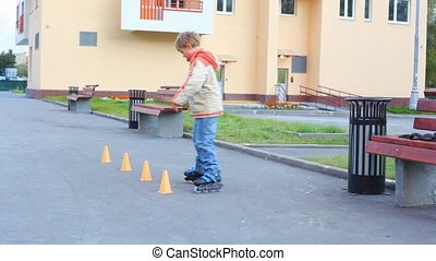 boy rollerblading in city past cone shells by figure of...
