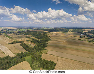 Aerial view of the blue sky and village harvest fields at summer time in Poland