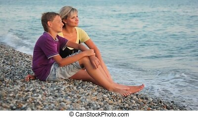 smiling woman and young boy sits on pebble beach and looks at sea