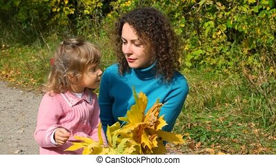 woung woman and little girl sitting in autumn park