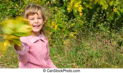 little girl playing with autumn leaves outdoors