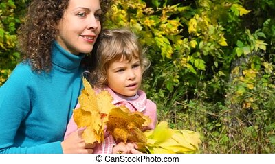 woung woman and little girl with leaves sitting in autumn park