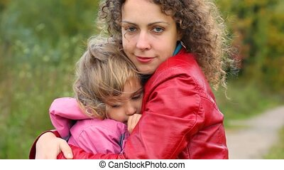 young woman hugs little girl in the wind outdoors
