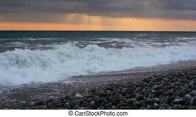 sea surf on pebble coast under sunset sky with rain clouds