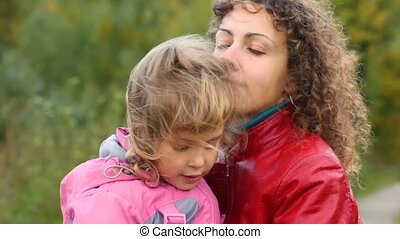young woman hugs little daughter in the wind outdoors