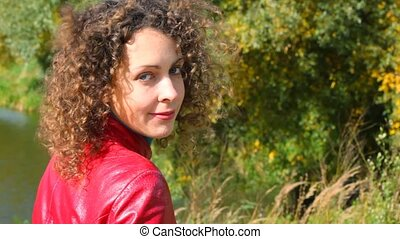 portrait of young smiling curly-headed woman turn round at...