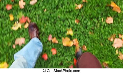 man and woman walking on green grass with autumn leaves, view to foots