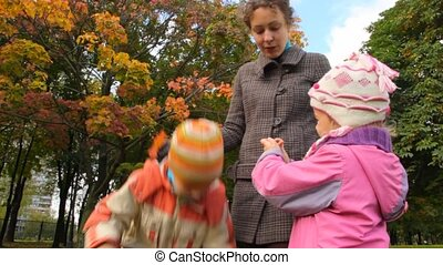 young mother talking with her daughter and son standing in park