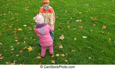 boy and little girl spinning on green grass with autumn...