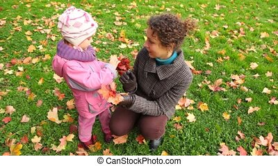 smiling young woman and little girl with autumn maple leaves