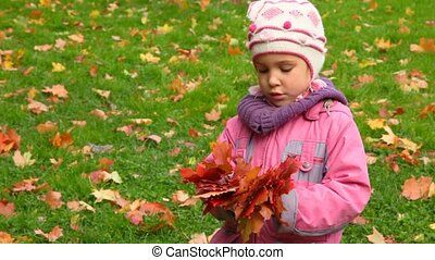 little girl with red autumn maple leaves, green grass in background
