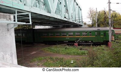 commuter train passes quickly under iron bridge in autumn