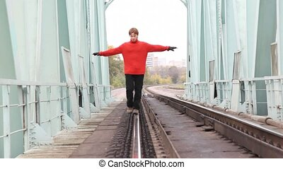 red-haired young man step back on rail on bridge, broadly...