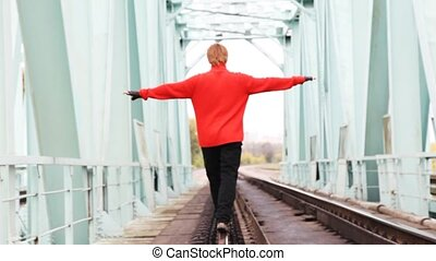red-haired young man step forward on rail on bridge, broadly...